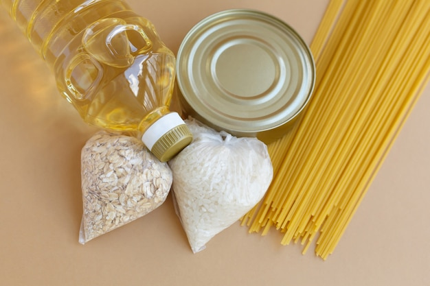 Zapas żywności zestaw artykułów pierwszej potrzeby dla potrzebujących. owoce i warzywa w puszkach oraz olej z makaronu i zboża