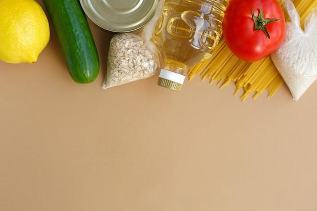 Zapas żywności zestaw niezbędnych produktów dla potrzebujących owoce i warzywa w puszkach oraz makaron masło i płatki zbożowe