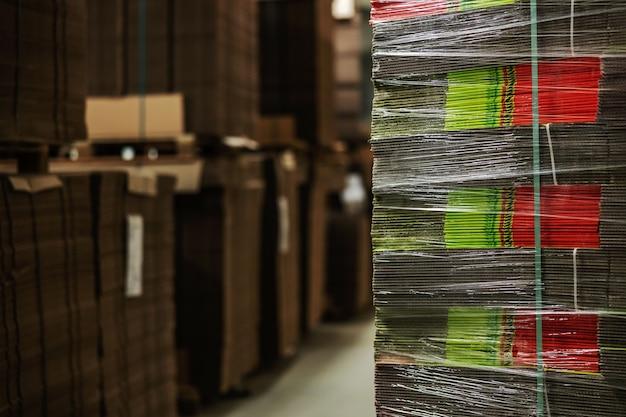 Zapasy nieopakowanych kartonów owiniętych przezroczystą folią stretch. zapasy tektury do pakowania świeżych owoców i warzyw. zapasy surowców i przygotowanie do sortowania