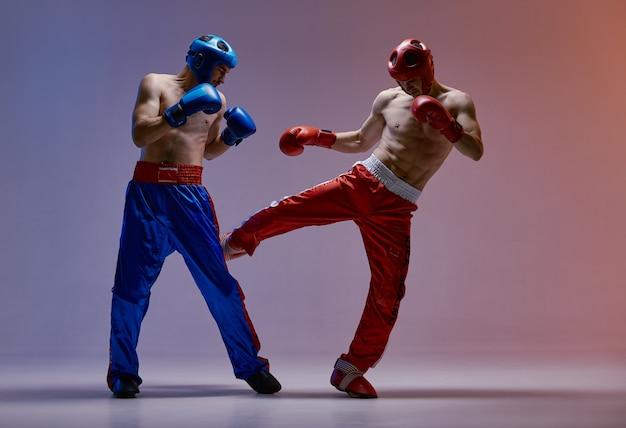 Zapasy walczących bokserów facetów w hełmach, rękawicach bokserskich w niebieskim czerwonym świetle w studio