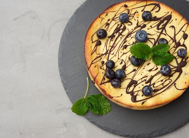 Zapiekana twaróg zapiekanka na czarnej płycie, widok z góry, smaczny i zdrowy deser