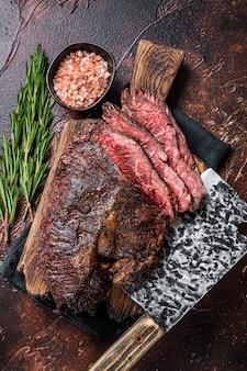 Zapiekana wisząca polędwica lub pokrojony stek wołowy onglet na desce rzeźniczej z tasakiem