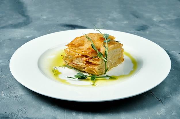 Zapiekana zapiekanka ziemniaczana ze śmietaną i serem na białym talerzu na betonowej powierzchni