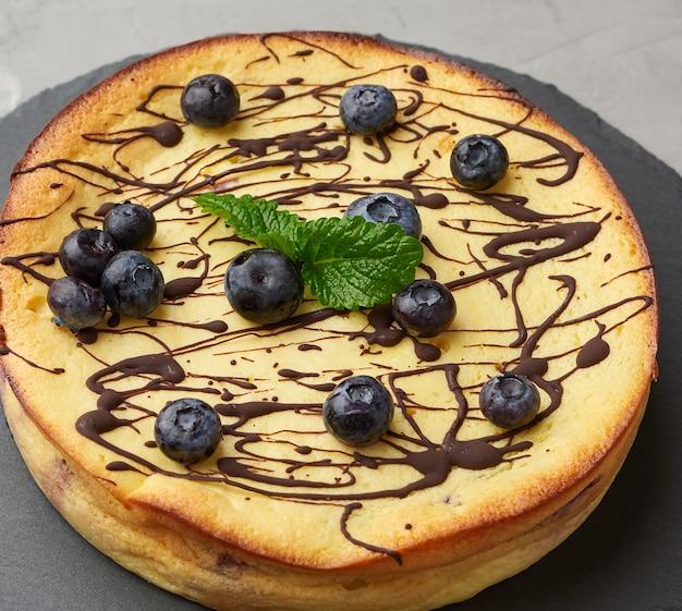 Zapiekane okrągłe zapiekanka z serem na czarnej płycie, widok z góry
