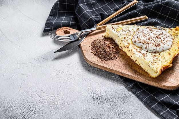 Zapiekanka twarogowa z organicznego twarogu na drewnianej desce do krojenia.