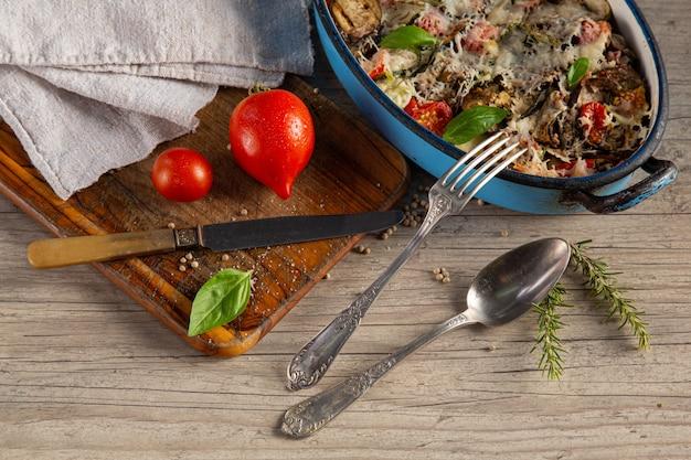Zapiekanka warzywna w naczyniu na desce do krojenia