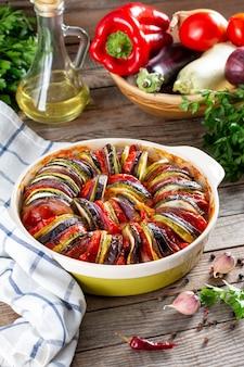 Zapiekanka z ratatouille na drewnianym stole. kolorowe warstwy świeżych letnich warzyw: cukinia, bakłażan, pomidory i ziemniaki. zdrowe wegańskie, wegetariańskie danie. menu, przepis