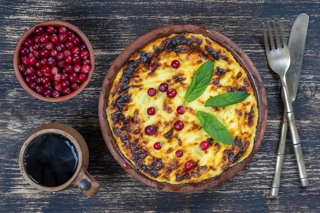 Zapiekanka z serem słodkim z rodzynkami i kaszą manną na drewnianym stole. ceramiczna miska z zapiekanym twarogiem, zbliżenie, widok z góry