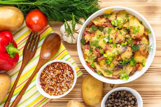 Zapiekanka ziemniaczana na drewnianym stole z warzywami. widok z góry.