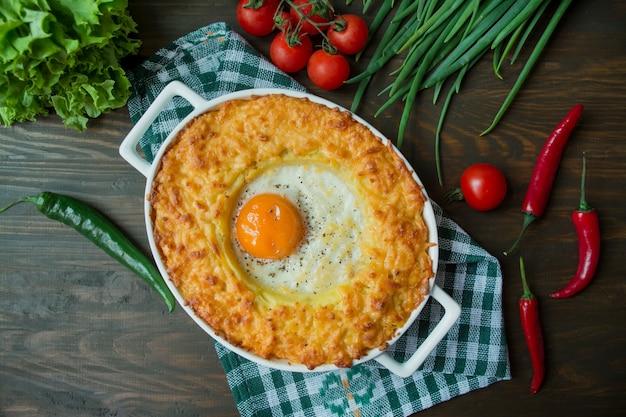 Zapiekanka ziemniaczana z bolognese. zapiekana zapiekanka ziemniaczana z jajkiem i tartym serem w ceramicznej owalnej blasze do pieczenia. drewniane ciemne tło.