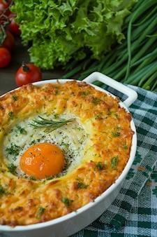 Zapiekanka ziemniaczana z bolognese. zapiekana zapiekanka ziemniaczana z jajkiem i tartym serem w ceramicznej owalnej blasze do pieczenia.