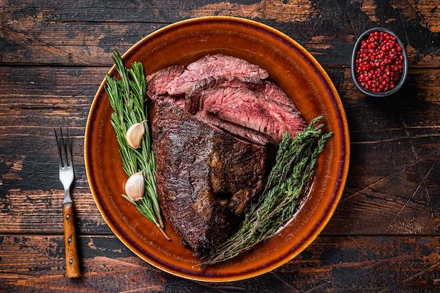 Zapiekany wieszak lub pokrojony stek wołowy onglet na rustykalnym talerzu z tasakiem. ciemne drewniane tło. widok z góry.