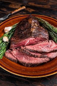 Zapiekany wieszak lub pokrojony stek wołowy onglet na rustykalnym talerzu z tasakiem