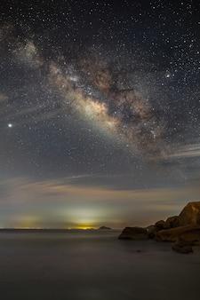 Zapierająca dech w piersiach sceneria drogi mlecznej na malowniczym nocnym niebie nad morskim krajobrazem