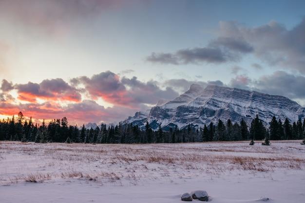 Zapierająca dech w piersiach sceneria górskiego krajobrazu pokrytego śniegiem pod pięknym niebem zachodzącego słońca