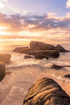 Zapierająca dech w piersiach sceneria kamienistej plaży o pięknym zachodzie słońca