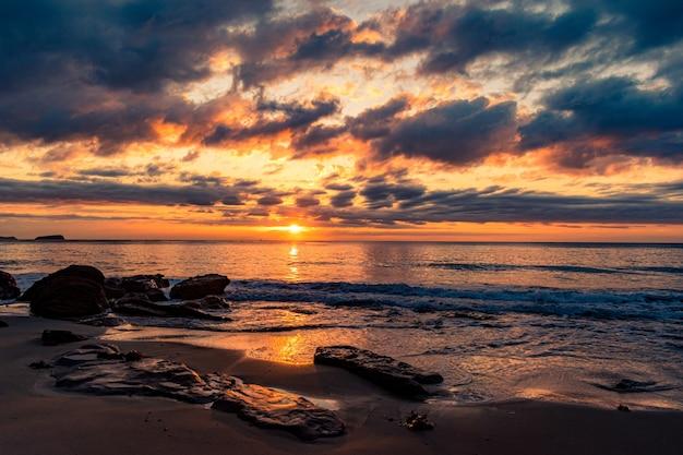 Zapierająca dech w piersiach sceneria piaszczystej plaży o pięknym zachodzie słońca
