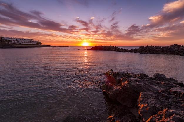 Zapierająca dech w piersiach sceneria pięknego zachodu słońca i kolorowe pochmurne niebo odbite w morzu