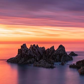 Zapierająca dech w piersiach sceneria stosów morskich podczas zachodu słońca pod kolorowym niebem na guernsey
