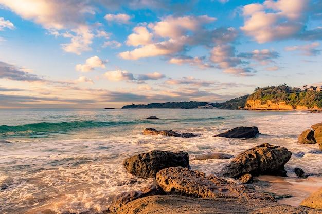 Zapierające dech w piersiach krajobrazy kamienistej plaży na pięknym zachodzie słońca