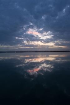 Zapierające dech w piersiach krajobrazy nieba zachodzącego słońca z chmurami burzowymi odbijającymi się na powierzchni wody