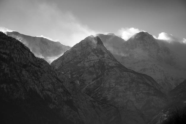 Zapierające dech w piersiach krajobrazy ośnieżonych gór pod malowniczym pochmurnym niebem