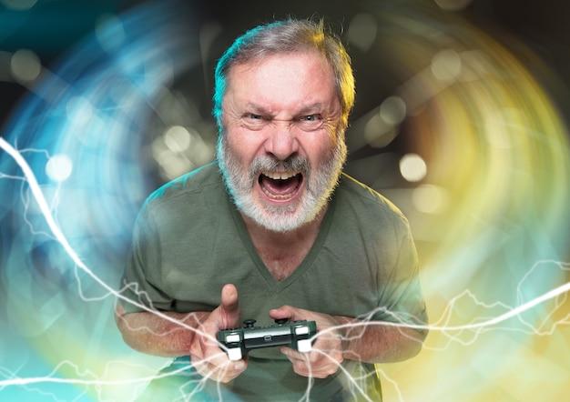 Zapierające dech w piersiach nowe życie. starszy mężczyzna posiadający kontroler gier wideo na białym tle na kolorowym tle. pełen emocji. spędzania wolnego czasu. ma najgorszy zespół gier wideo. próbuję osiągnąć najwyższy poziom.
