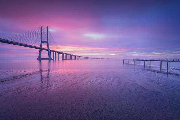 Zapierające dech w piersiach ujęcie mostu vasco da gama o wschodzie słońca w lizbonie, portugalia