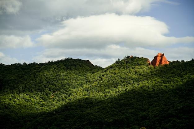 Zapierające dech w piersiach ujęcie niesamowitego krajobrazu wzgórza w świetle słonecznym i pochmurnym niebie