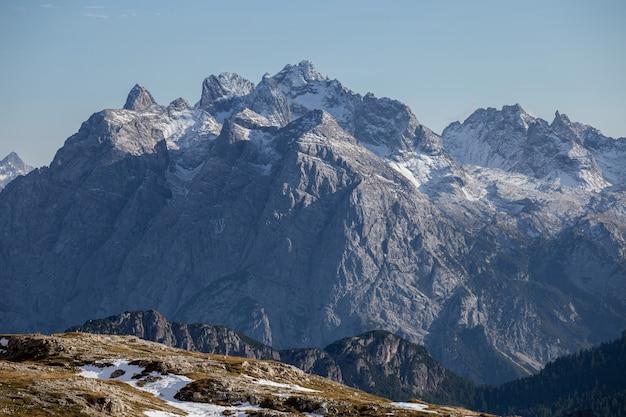 Zapierające dech w piersiach ujęcie śnieżnych skał we włoskich alpach pod jasnym niebem