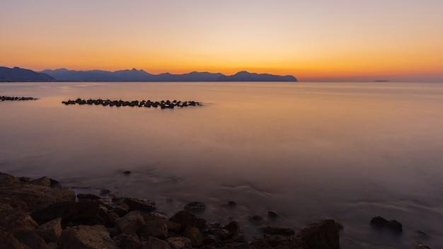 Zapierające dech w piersiach ujęcie spokojnego morza i skalistego brzegu podczas zachodu słońca
