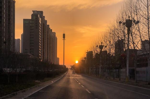 Zapierające dech w piersiach ujęcie zachodzącego słońca wzdłuż ulicy w środku nowoczesnego miasta