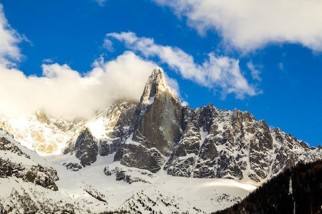 Zapierające dech w piersiach widok na szczyt mont blanc pokryty błyszczącym śniegiem, lodem i lodowcami pod błękitne niebo z bufiastymi białymi chmurami po francuskiej stronie alp w pogodny zimowy, słoneczny, zimowy dzień