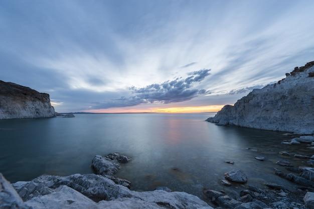 Zapierające dech w piersiach zdjęcie oceanu z ośnieżonymi wzgórzami po bokach i piękną sceną zachodu słońca