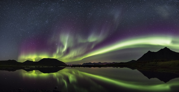 Zapierający dech w piersiach strzał wiatr kolory odbija w morzu na lofoten, norwegia