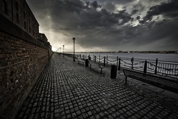 Zapierający dech w piersiach strzał z chodnika w pobliżu morza w liverpoolu w pochmurny dzień