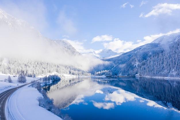 Zapierający dech w piersiach widok na jezioro i odbicie nieba na nim uchwycone zimą
