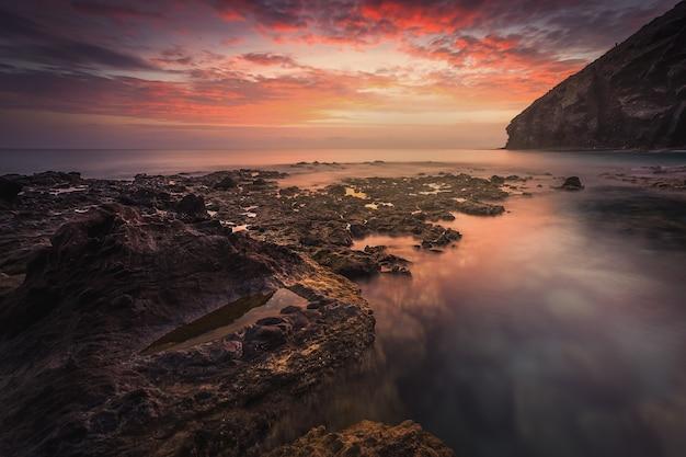 Zapierający dech w piersiach widok na morze i skały na malowniczym dramatycznym zachodzie słońca