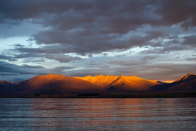 Zapierający dech w piersiach widok na odbijające się morze na tle majestatycznego pasma górskiego