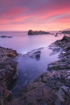 Zapierający dech w piersiach widok na pejzaż morski i skały o malowniczym, dramatycznym zachodzie słońca
