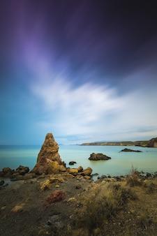 Zapierający dech w piersiach widok na pejzaż morski i skały pod malowniczym pochmurnym niebem