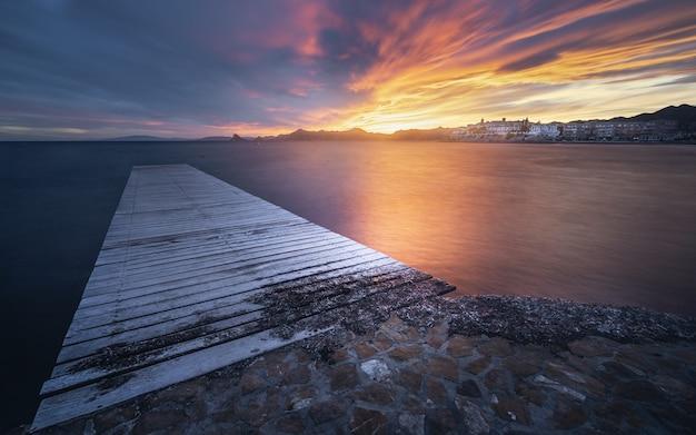 Zapierający dech w piersiach widok na pejzaż morski z drewnianym molo o malowniczym dramatycznym zachodzie słońca