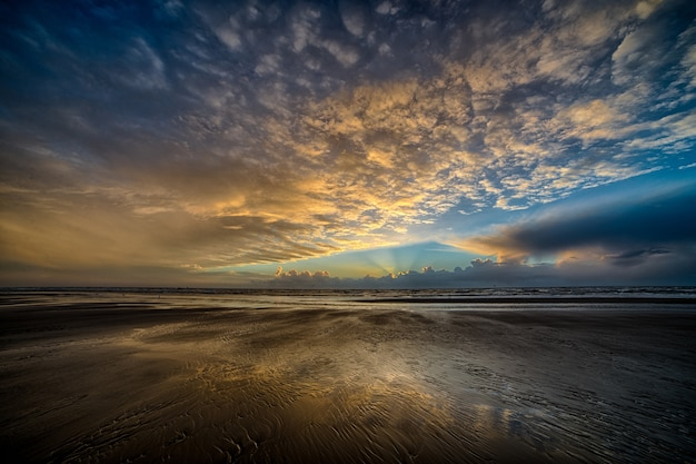 Zapierający dech w piersiach widok na piękny, pochmurny, kolorowy sufit nad brzegiem oceanu