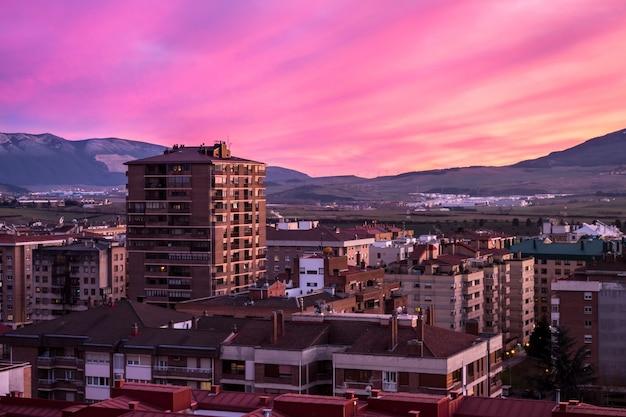Zapierający dech w piersiach widok na różowy zachód słońca i miasto