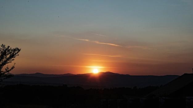 Zapierający dech w piersiach widok na zachód słońca i sylwetki