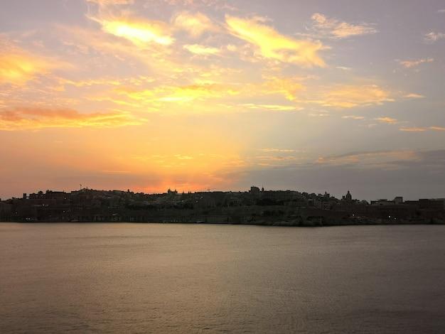 Zapierający dech w piersiach widok na zachód słońca na plaży otoczonej drzewami na malcie