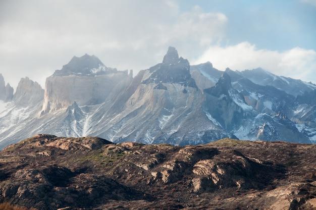 Zapierający dech w piersiach widok na zaśnieżone góry pod zachmurzonym niebem w patagonii w chile