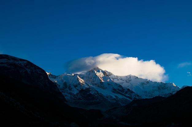 Zapierający dech w piersiach widok na zaśnieżony szczyt góry na błękitnym niebie