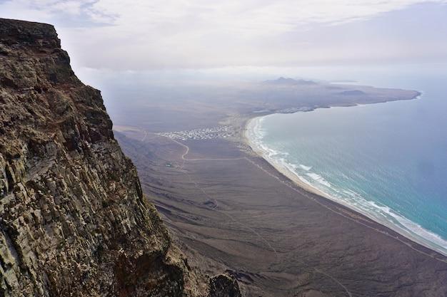 Zapierający dech w piersiach widok z el risco de famara, zwiedzanie punktu nad plażą caleta de famara w lanzarote, wyspy kanaryjskie, hiszpania.