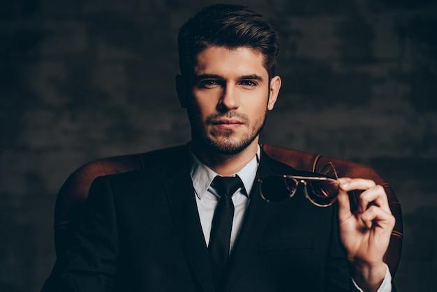 Zapierający dech w piersiach wygląd. portret młodego przystojnego mężczyzny w garniturze, trzymającego okulary przeciwsłoneczne i patrzącego na kamerę siedząc w skórzanym fotelu na ciemnoszarym tle